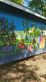 shed painted with flowers and gardening items