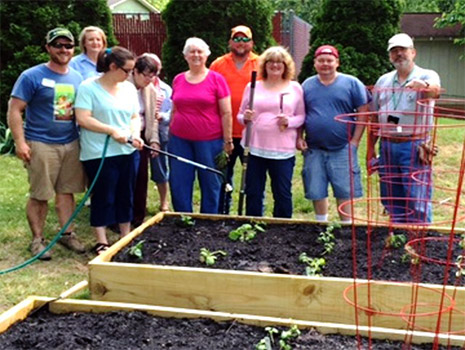 master gardeners posing in front of their raised gardening beds